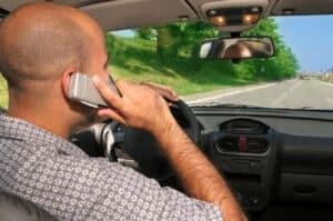 Mann telefoniert mit Handy am Steuer