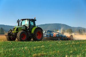 Auf einer Landstraße können Landwirtschaftsfahrzeuge wie z. B. Traktoren unterwegs sein. Vorsicht ist daher geboten.