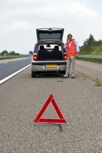 Mann stellt nach Unfall ein Warndreieck auf