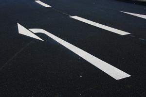 Markierungen sind eine Kategorie der Verkehrszeichen. Pfeilmarkierungen geben z. B. die Fahrtrichtung an.